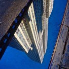 Empire State Building reflected in puddle