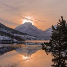 Winter morning. Thin, high haze on the sky and patches of ice on a calm fjord. The mountain Ryssdalshorn - Norway