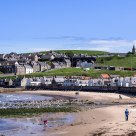 Enjoying the beach life. People and a few hundred seagulls. The town of Cullen - Scotland.