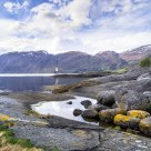 Stones in tidal pond. View towards the Anda Lighthouse in Nordfjord - Norway