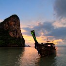 Longtail boats at sunset off Railay Beach, Krabi Thailand