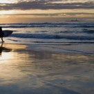 Surfer enjoying the waves in the setting sun